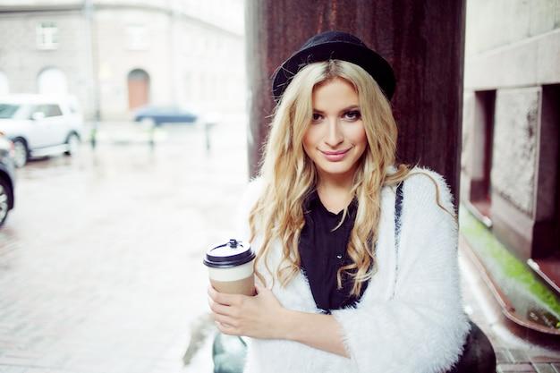 Жизнерадостная женщина на улице пить утренний кофе.
