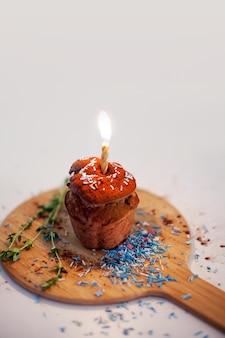 Вкусный праздничный кекс со свечой на столе