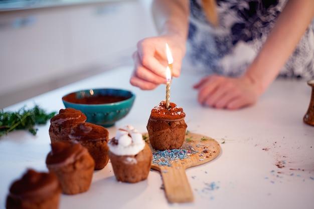 女の子はカップケーキのろうそくを点灯します