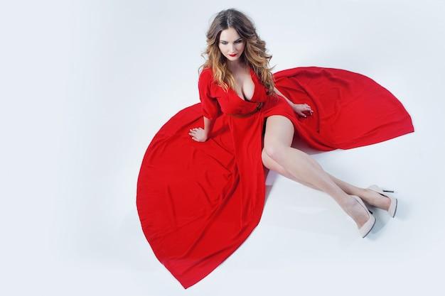 赤いドレスの若い壮大な女性のファッション写真