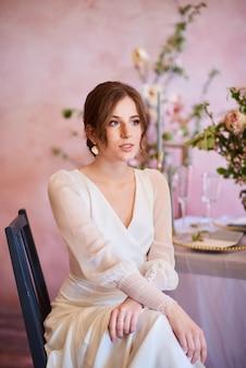 美しい白いドレスを着たモダンな花嫁。そばかすのある優しい花嫁が宴会エリアの結婚式のテーブルに思慮深く座っています。