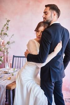 ちょうど夫婦が抱擁します。バンケットエリアの結婚式のテーブルで美しい新郎新婦。ロマンチックな瞬間にスタイリッシュな新婚夫婦の肖像画
