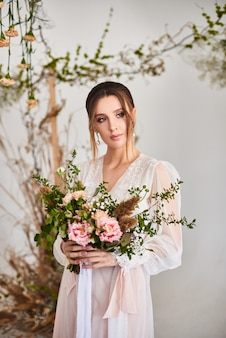 大きくて美しいカラフルなワイルドフラワーのウェディングブーケを持った非常に素敵な若い女性。繊細なランジェリーを着た花嫁の手に繊細なウェディングブーケ