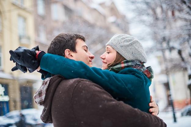 雪の公園の外の冬の休暇休暇中に一緒に遊び心のある幸せなカップル