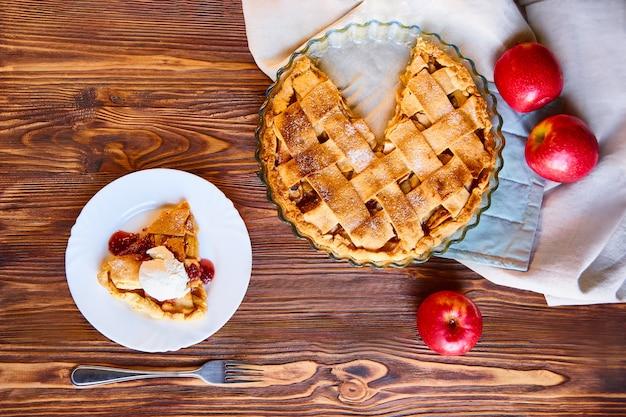 Вкусная домашняя композиция яблочного пирога. сырые яблоки на льняном полотенце. макет или натюрморт с самодельной шарлоткой в форме для приготовления пищи
