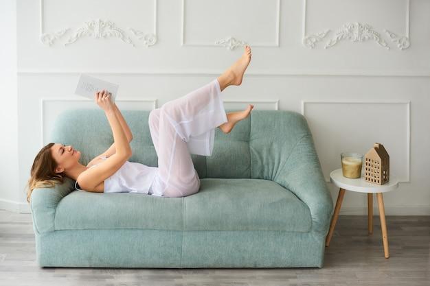 Женщина остается дома и развлекается с интересной книгой на современном диване у себя дома