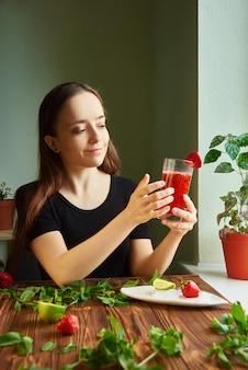 Приготовьте дома прохладный летний коктейль с клубникой, лаймом и мятой. молодая девушка доброе утро здоровый завтрак смузи напиток из супер продуктов, фруктов, ягод