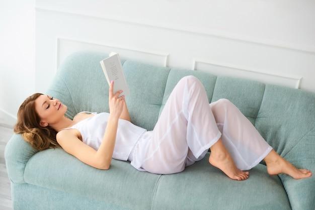 Женщина в домашней одежде остается дома и читает книгу, лежа на диване. девушка отдыхает дома и дурачится