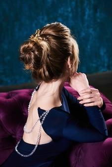 美しい明るい髪の若い女性はソファの後ろに寄りかかった