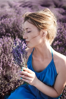 Молодая женщина в романтическое голубое платье отдохнуть в лавандовых полей. романтическая девушка мечтает в цветах лаванды. флорист собирает цветы для букета