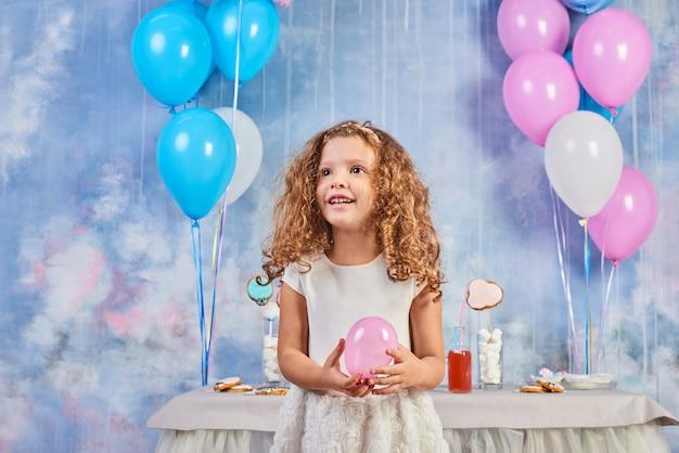 風船で飾られた部屋で子供の面白い誕生日パーティー。幸せな少女は、国際子供の日を祝います。面白い子が家で遊ぶ