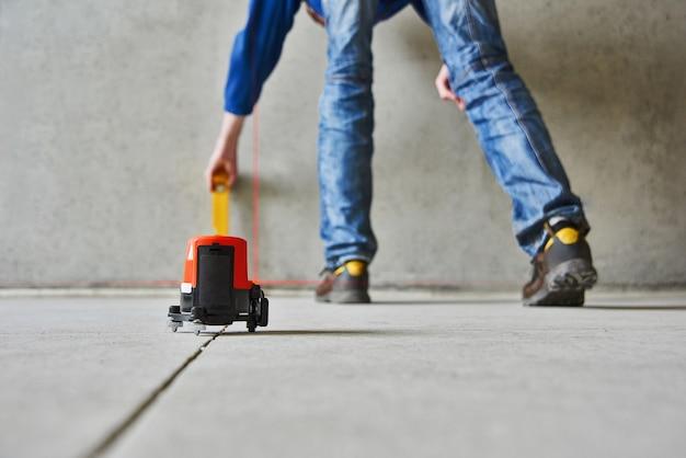 レーザーレベルチェックの床と壁を持つ男