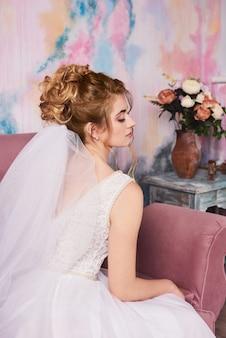 白いウェディングドレスの花嫁は、家での朝の集まり中に新郎を待ちます