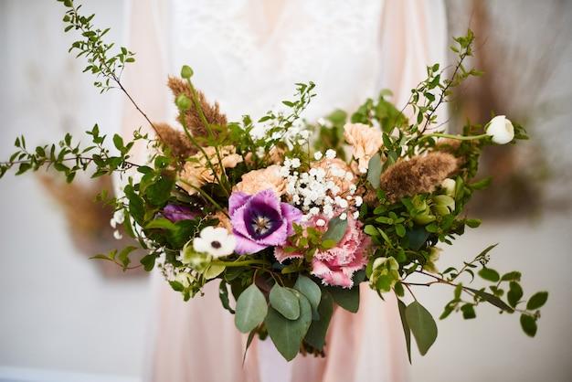 大きくて美しいスタイリッシュなウェディングブーケを保持している女性。結婚式の花の装飾で色とりどりの花。朝の花嫁