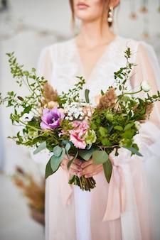 大きくて美しいカラフルな花のウェディングブーケを持ってとても素敵な若い女性。朝の花嫁