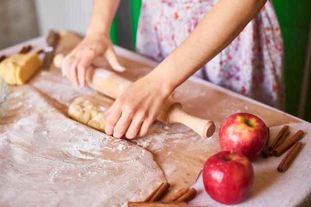 Руки работают с тестом приготовления рецепта хлеба. женские руки, делая тесто для пиццы. женские руки раскатывают тесто. мама раскатывает тесто на кухонной доске скалкой