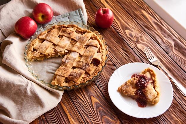木製のテーブルに自家製のおいしいアップルパイと組成。りんご。リネンタオル。