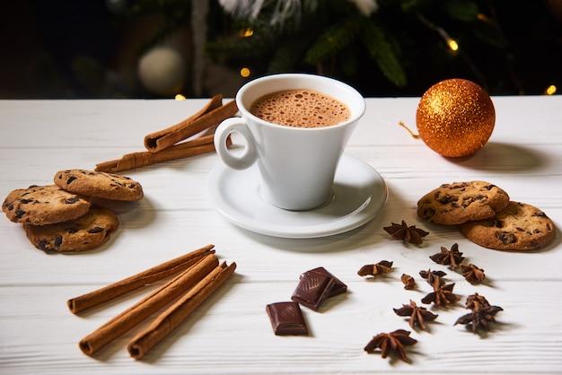 コーヒーとクリスマスに白いテーブルの上のクッキー