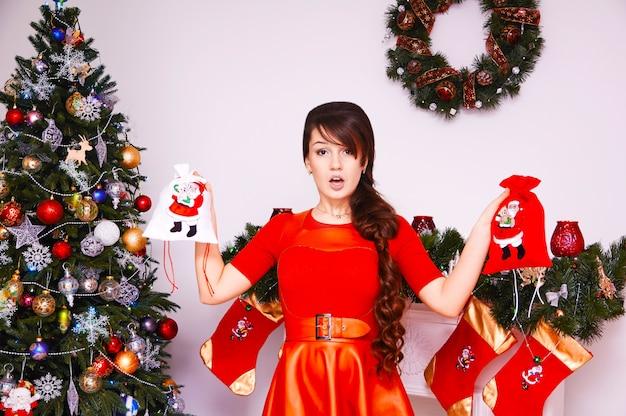 メリークリスマスと新年あけましておめでとうございます!プレゼントと陽気なかわいい若い女性。かわいい女の子はクリスマスツリーの近くの贈り物を屋内で保持します