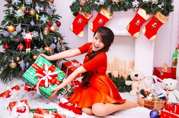 メリークリスマスと新年あけましておめでとうございます!プレゼントと陽気なかわいい若い女性。かわいい女の子は屋内でクリスマスツリーの近くに大きな贈り物を保持します