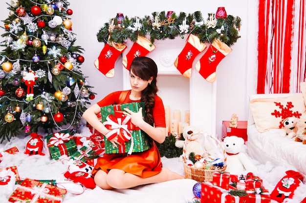 メリークリスマスと新年あけましておめでとうございます!プレゼントボックスとクリスマスのギフトを持つ若い女性が家を飾った