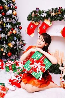 メリークリスマスと新年あけましておめでとうございます!プレゼントと陽気なかわいい若い女性。かわいい女の子が屋内でクリスマスツリーの近くのギフトを保持します