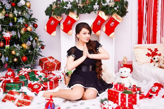 メリークリスマスと新年あけましておめでとうございます!プレゼントと陽気なかわいい若い女性。屋内のクリスマスツリーの近くに座っているきれいな女の子