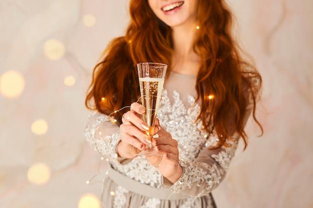 メリークリスマスと新年あけましておめでとうございます!陽気なかわいい若い女性はシャンパングラスを保持し、屋内でクリスマスを祝福