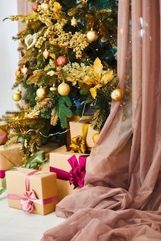 黄金のおもちゃで飾られたクリスマスと新年のツリー。ホリデーデコレーションルーム