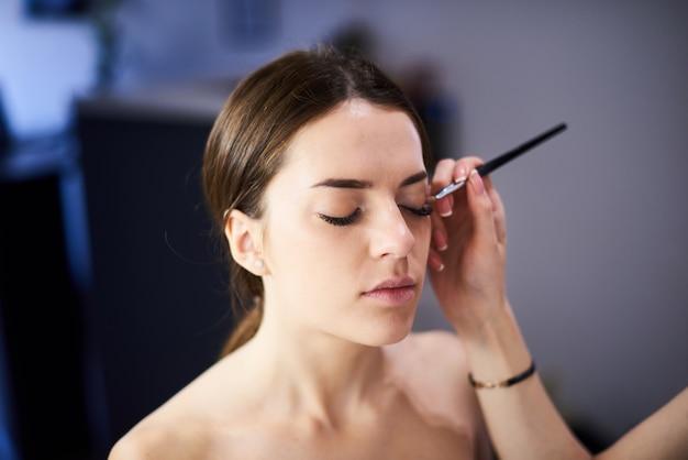 Визажист делает идеальный макияж для молодой модели