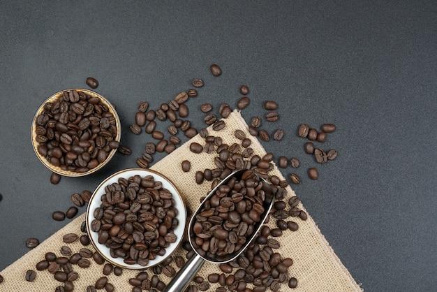 Коричневые жареные кофейные зерна и кофейная чашка