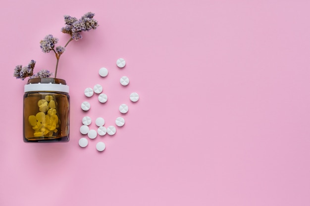 Бутылка лекарств и разбросанные таблетки на пастельных розовом фоне. разорвал витамины на ярком фоне. целебные травы.