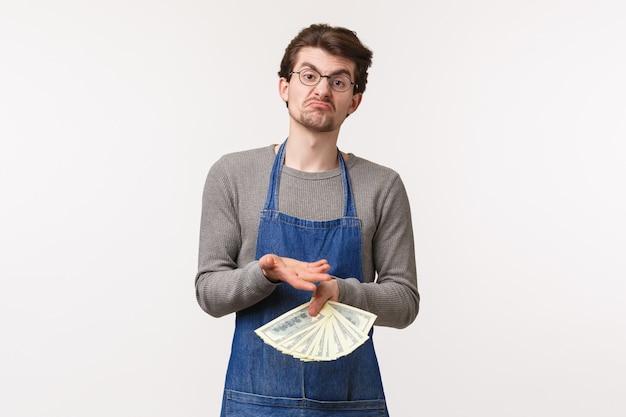 中小企業、金融、キャリアのコンセプト。肩をすくめて顔をゆがめたエプロン姿の優柔不断な若い男性の肖像画はお金を保持し、利益のために現金を投資する方法を知らない