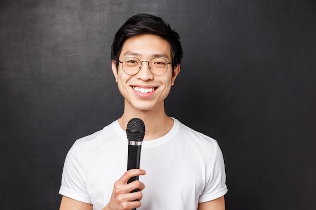 Досуг, люди и музыкальная концепция. красивый и милый улыбающийся азиатский мужчина в белой футболке, очках, с микрофоном, поющий на караоке-вечеринке с друзьями, выбирающий песню на экране,