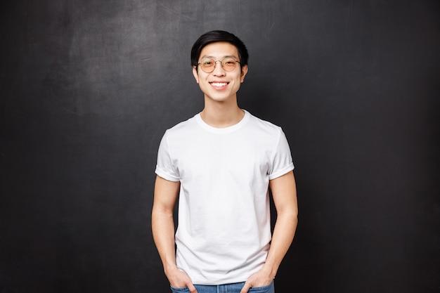 Портрет молодого азиатского парня в очках, стоя в белой повседневной рубашке, дружелюбно улыбаясь, выражать счастливые восторженные эмоции, висит с товарищами после колледжа