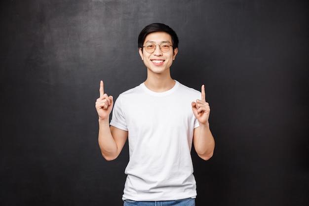 Портрет радостного красивого улыбающегося азиатского хипстерского парня в белой рубашке и солнечных очках, указывающего пальцами на советы, посмотрите, посетите этот веб-сайт или прочитайте баннер компании с классной рекламой,