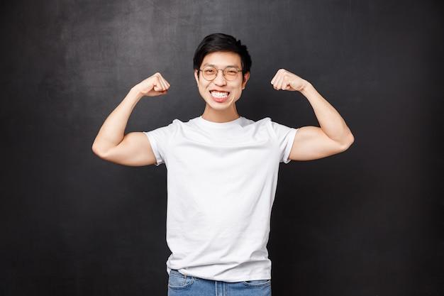 Спорт, спортсмены и олимпийские игры концепции. веселый и сильный молодой красивый парень хвастался своей силой, готовился к лету, сгибал бицепс и улыбался довольный,