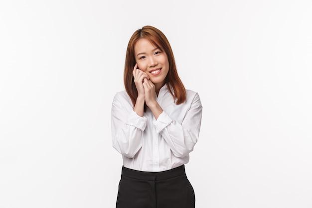 Нежность, красота и бизнес-концепция. нежная обаятельная азиатка, офисная леди в белой рубашке и черной юбке, нежно касаясь ее лица и восхищенно улыбающаяся, наносит макияж, ухаживает за кожей