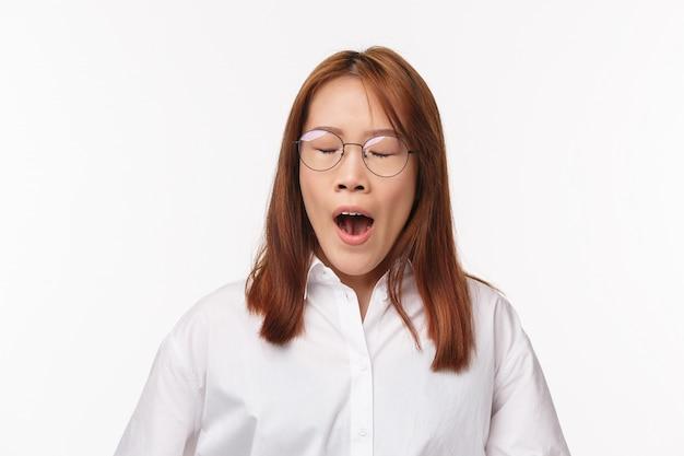 Крупным планом портрет усталой азиатской офисной леди, женщины, зевающей с закрытыми глазами, рано просыпающейся, предприниматель нуждается в кофе, чтобы получить энергию, носить очки, работать над проектом поздно, стоять
