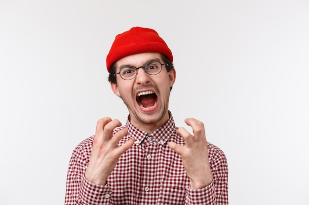 口ひげを持つ苦しめられて怒っている若い面白い流行に敏感な男のクローズアップの肖像画は、赤いビーニーを着用し、眼鏡をかけ、腹を立てて悩まされ、腹を立てた気持ちから叫んで、