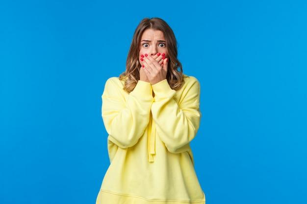 Потрясенная, потерявшая дар речи и взволнованная молодая женщина, видящая несчастный случай, ужасающую сцену в кино, прикрывает рот руками, чтобы не кричать, смотрит испуганными глазами на камеру
