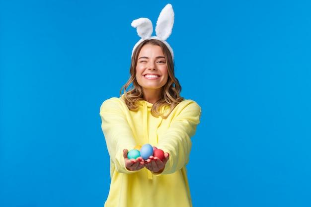 Концепция праздники, люди и эмоции. нежная милая блондинка кавказской девушки дарит вам пасхальные яйца с сияющей приятной улыбкой, в кроличьих ушах, празднует религиозный праздник