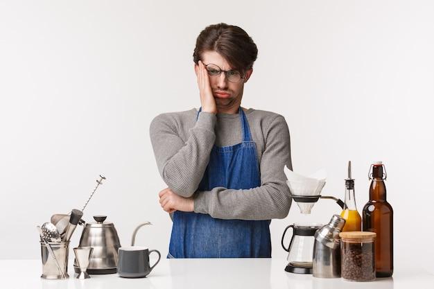 バリスタ、カフェワーカー、バーテンダーのコンセプト。エプロンで苦しんで困っている若い男性の肖像画は、コーヒーの作り方を知らない、コーヒーの作り方を学ぶのに苦労している、ため息をつく