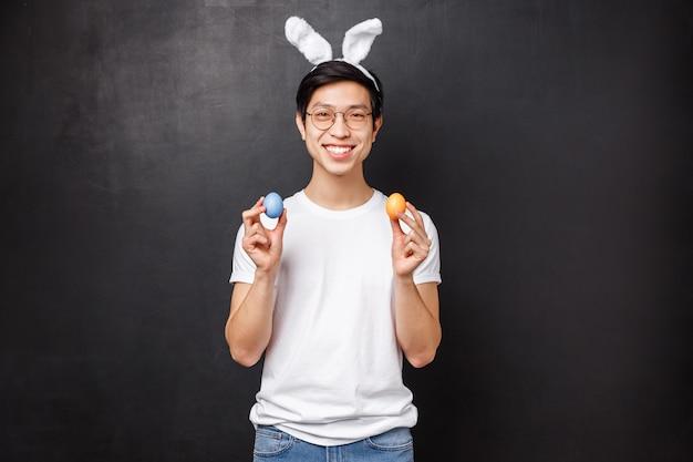 Праздники, вечеринки и концепция пасхи. портрет счастливого улыбающегося дружелюбного азиатского парня в ушах кролика, празднующего православный святой день, держа крашеные яйца и глядя в камеру, стенд