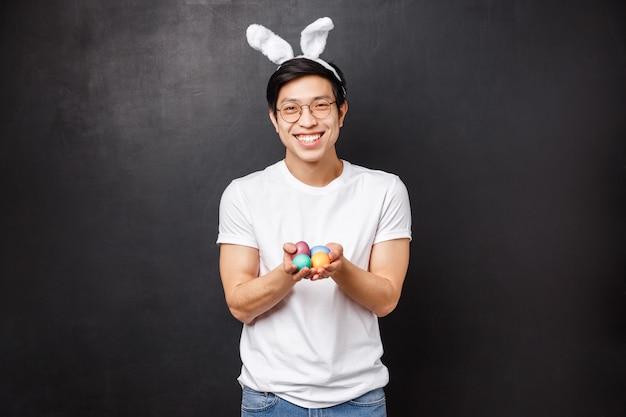 Праздники, вечеринки и концепция пасхи. портрет нежного дружелюбного улыбающегося азиатского парня в ушах кролика, дающего тебе крашеные яйца как угощение в день православного празднования, стенд