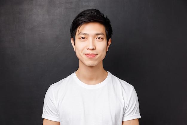Портрет крупным планом улыбающегося дружелюбно выглядящего молодого азиатского мужчины модели в белой футболке, глядя на камеру и ухмыляясь, стоя над, концепция эмоций людей и образ жизни