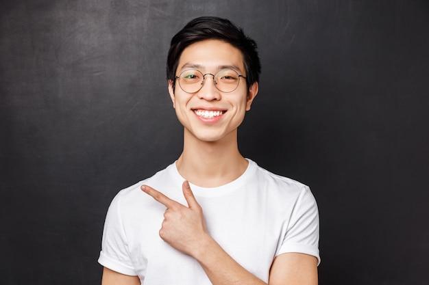 Крупным планом портрет веселого молодого парня, начинающего свое дело на интернет-платформе, в очках, указывая пальцем влево и улыбаясь, дает рекомендации, предлагает посетить веб-страницу