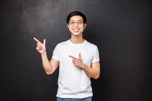Портрет симпатичного молодого азиатского мужчины, студента в белой рубашке, указывающего пальцами в верхнем левом углу на промо, скидку или баннер, улыбающуюся камеру, предлагает ссылку для посещения,