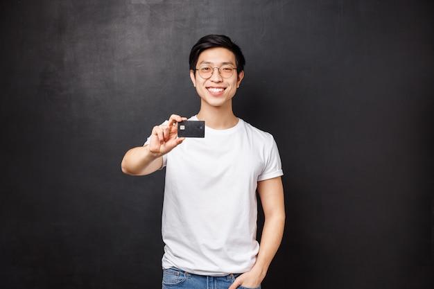 Концепция банка, финансов и оплаты. портрет дружелюбного уверенно молодого азиатского мужчины показывая кредитную карточку на камере с довольной сияющей улыбкой, счет совета открытый на положенных деньгах,