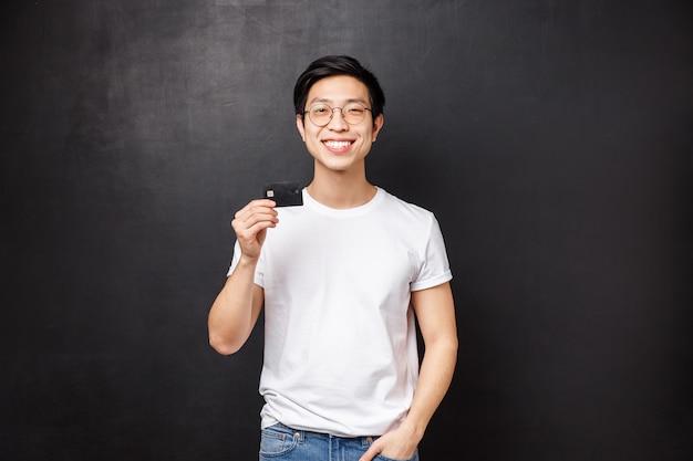 Концепция банка, финансов и оплаты. портрет довольного харизматичного азиатского парня в футболке и очках, рекомендую положить деньги на депозит, довольный банковским обслуживанием, взять кредитную карту и улыбаться